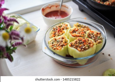 Cooking stuffed peppers with rice, lentils and vegetables cooked with tomato sauce in oven in glass tray