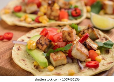 Cooking taco with tofu. Mouth-watering meatless snack with fresh vegetables, herbs and tortilla. Vegan recipe of Mexican dish.