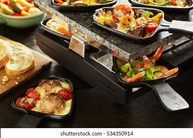 Cooking a tasty meal of melted raclette cheese with assorted ingredients in individual skillets on an electric griddle with mushrooms, sweet pepper and prawns