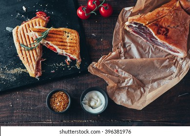 cooking tasty panini with ham covered with cheese, tomatoes and flavoring