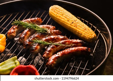 Cooking of tasty sausages and vegetables on barbecue grill, closeup