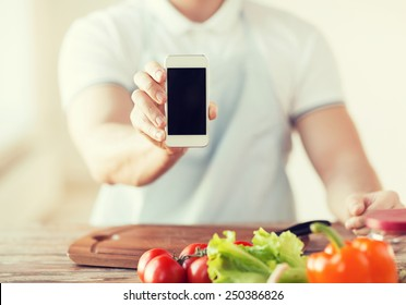 cooking, technology, advertising and home concept - close up of male hands holding smartphone with blank black screen