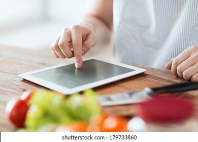 cooking, technology and home concept - closeup of man pointing finger to tablet pc computer