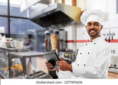 cooking, technology and people concept - happy male indian chef in toque with tablet computer over kebab shop kitchen background
