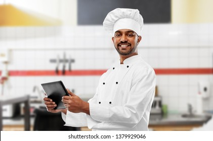 cooking, technology and people concept - happy male indian chef in toque with tablet computer over restaurant kitchen background