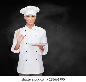 cooking, technology and people concept - smiling female chef, cook or baker with tablet pc computer showing ok gesture over blackboard background