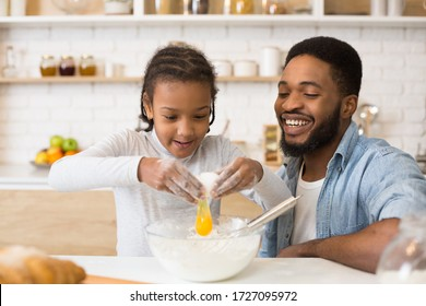 Cooking together at home. Excited african girl adding egg to cookies dough, cheerful dad watching her, copy space