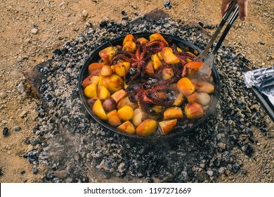Cooking traditional balkan turkish bosnian dalmatian meal Peka in metal pots called sac sach or sache. Detail of squid or octopus with potatoes under Sache. Sac is covered with hot charcoal.