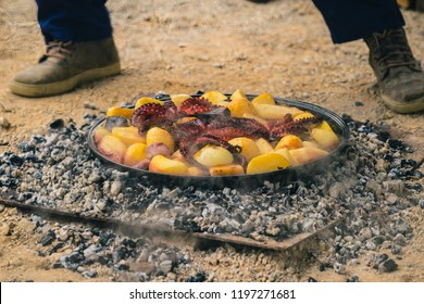 Cooking traditional balkan turkish bosnian dalmatian meal Peka in metal pots called sac sach or sache. Squid or octopus with potatoes under Sache. Sac is covered with hot charcoal.