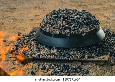 Cooking traditional balkan turkish bosnian dalmatian meal Peka in metal pots called sac sach or sache. Detail Sac which is covered with hot charcoal.