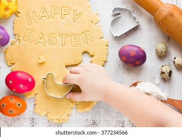 Cooking traditional Easter biscuits. Kid hands cut cookie from raw dough on a white table with colorful eggs and cake cutters. Easter food concept