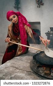 Cooking traditional Turkish borek, pide, pita or yufka bread. Traditional Turkish food. Woman preparing or making borek or bread dough on fire
