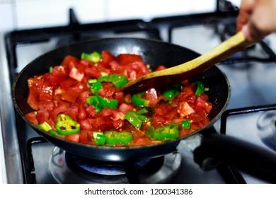 Cooking traditional turkish food menemen / tomatos and pepper in pan