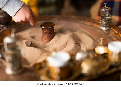 Cooking Turkish coffee in sand and a cezve. Turkish coffeee is a traditional hot drink in Turkey.