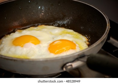 cooking two fried eggs in a pan, closeup