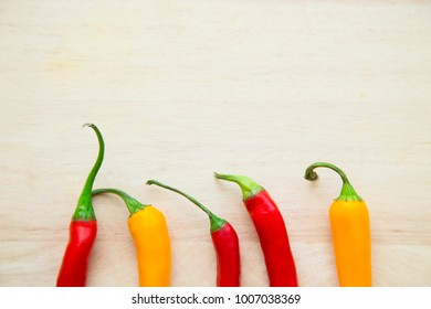 Cooking, Vegetarian, Vegan Concept.A light wooden background with red and yellow chili peppers with copy space, top view