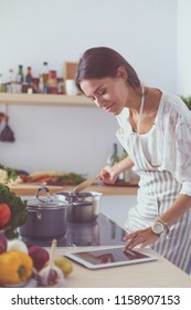 Cooking woman in kitchen with wooden spoon. Cooking woman