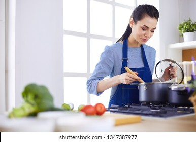 Cooking woman in kitchen with wooden spoon