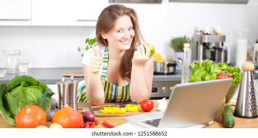 Cooking woman looking at computer while preparing food in kitchen