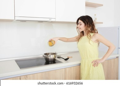 Cooking woman in a yellow dress in kitchen. sprinkles pasta with a glass jar in a metal pan.