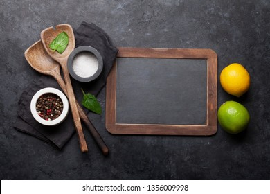 Cooking wooden utensils, condiments and spices on stone kitchen table. Food cooking template concept. Top view with blackboard for your text. Flat lay