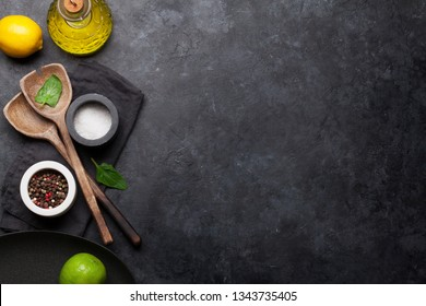 Cooking wooden utensils, empty plate, condiments and spices on stone kitchen table. Food cooking template concept. Top view with copy space. Flat lay