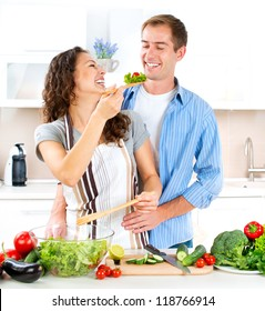 Cooking.Happy Couple Cooking Together - Man and Woman in their Kitchen at home Preparing Vegetable Salad.Diet.Dieting. Healthy Food