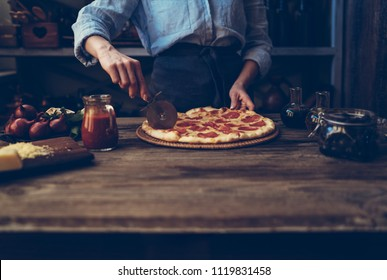 Cook's hands making homemade pizza on the table. Pizza with ingredients. Tomatoes, garlic, parsley, pepper, and parmesan cheese on dark wooden background. Food, family and people concept.