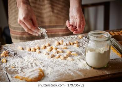 Cooks hands preparing raw pumpkin gnocchi