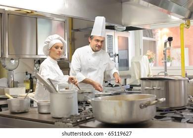 Cooks preparing food in restaurant kitchen