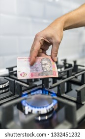 Cooktop with burning gas ring with hands holding money uah hryvnas for combustion at home.