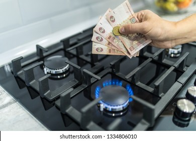 Cooktop with burning gas ring with hands holding money uah hryvnas for combustion .