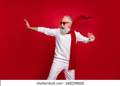 Cool aged santa like man drunk dancing with youth at club wear sun specs knitted clothes isolated red background