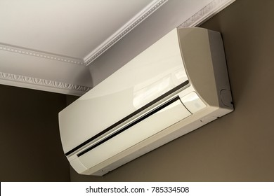 Cool air conditioner system on dark wall in room interior