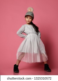 Cool asian fashion kid girl in black boots, pink dress and funny cap with fur pompon stands in cool pose on pink background