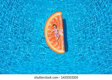 Cool baby girl with sunglasses is lying on a orange slice shaped float over blue pool water and enjoys a hot summer day