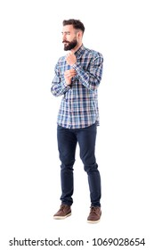 Cool bearded confident guy getting dressed buttoning sleeve button and looking away thoughtfully. Full body isolated on white background.