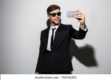 Cool bearded guy in black suit and suglasses taking selfie on mobile phone, isolated over white background