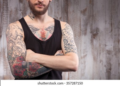 Cool bearded hipster is standing with crosses arms near a wall. The tattooed man is posing with confidence. Copy space in right side