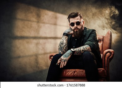 Cool bearded young man sitting on a vintage chair in a dark studio with smoke and window silhouette in the background