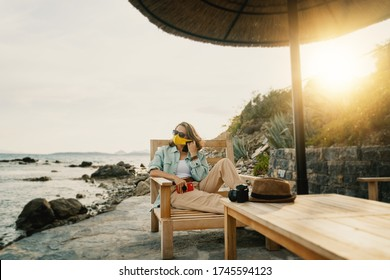Cool beautiful girl woman traveler by the sea with a mask on her face, stylish outfit, summer travel 2020 concept