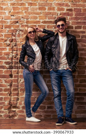 Cool Beautiful Young Couple In Leather Jackets And Sunglasses Is Looking At Camera Posing And Smiling Standing Against Brick Wall Image