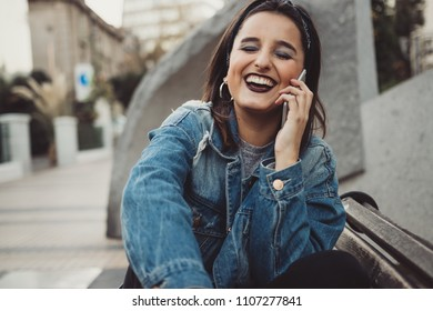 Cool and beautiful young woman speaking on the phone in the city. Urban style