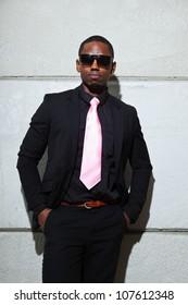 Cool black american man in dark suit wearing sunglasses. Fashion shot in urban setting.