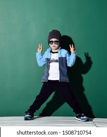Cool boy in blue sunglasses, headwear, fleece jacket, pants and sneakers is posing with his legs planted wide apart showing V victory sign with both hands on green
