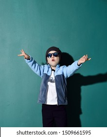 Cool boy in blue sunglasses, headwear, fleece jacket and pants is posing with his hands up, showing cool sign, saying cool on green background with free text copy space above