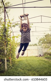 Cool boy swings on rope in the countryside, enjoying process.