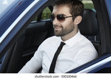 Cool businessman driving car, content