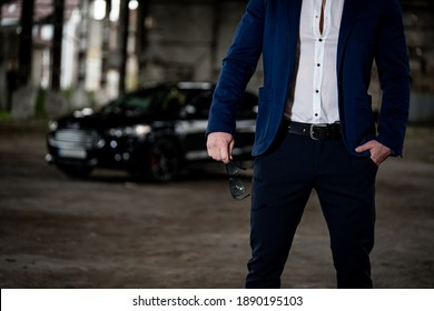 Cool businessman is standing on abandoned stockhouse background. Selective focus on unrecognizible fashion male.