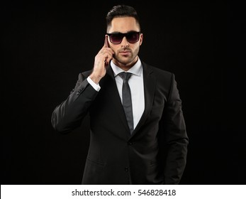 Cool businessman in sunglasses with exclusive mobile phone on a dark background